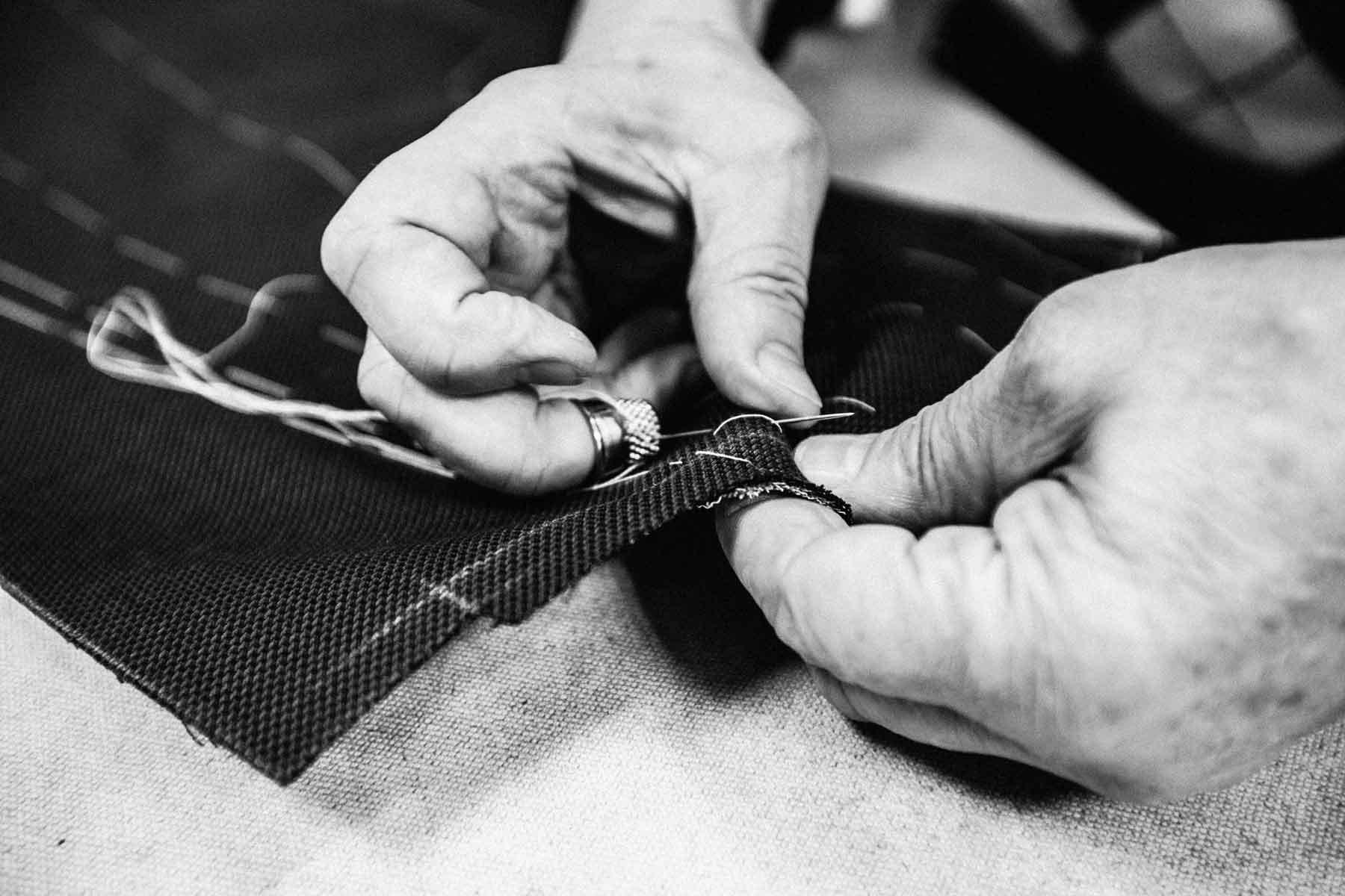 Nahaufnahme eines Schneiders beim einsetzen der Naht in ein Stück Stoff bei Monokel Berlin